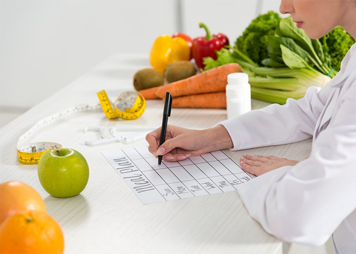 Woman writing out a Paleo diet meal plan on a piece of paper
