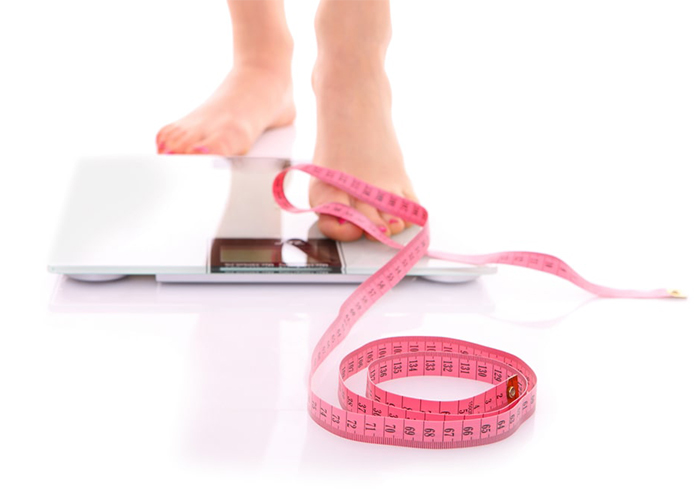 Woman on keto plateau using weight scale and measuring tape