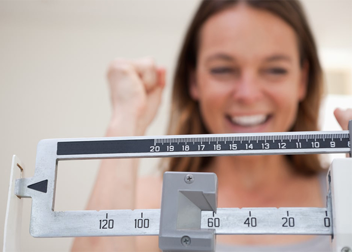 Woman on scale happy with ketosis weight loss