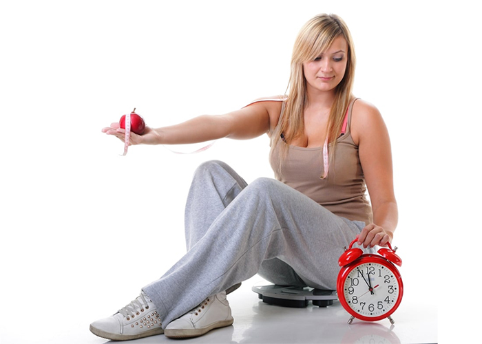 Woman looking at a clock wondering how long her Keto plateau will last