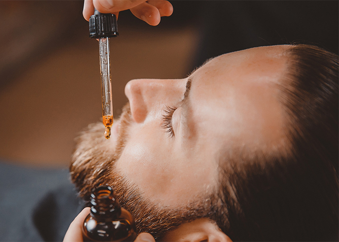 Barber applying a DIY Essential Oil Blends For Beard Oil in Beary Hairy scent