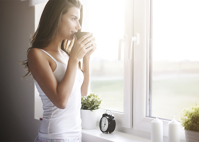 Woman at her window drinking a Keto-approved drink in a mug
