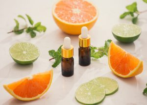 Bottles of ginger and citrus essential oil blend surrounded by cut oranges and lime