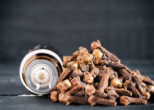 A bottle of ginger and clove essential oil blend next to a pile of cloves