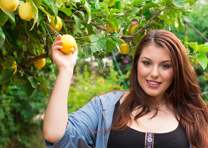 Woman in a garden holding a lemon from a lemon tree