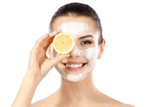 Woman in a face mask holding up half a lemon to her eye while smiling