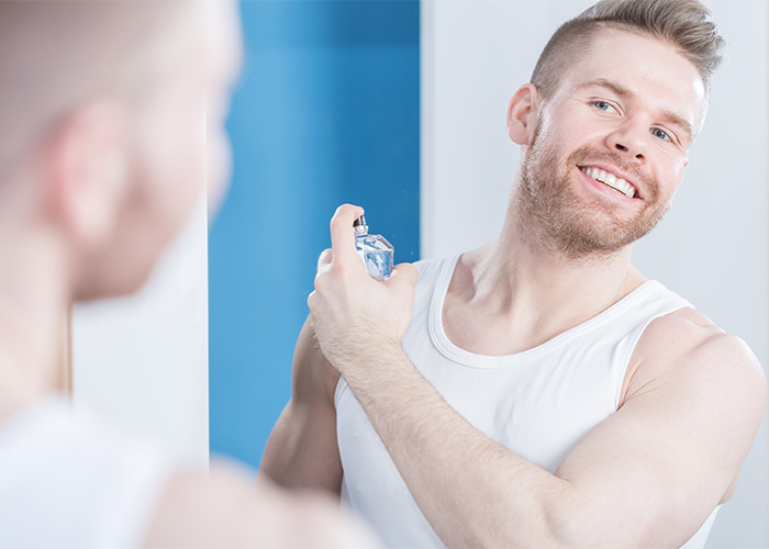Man spraying homemade essential oil cologne on his neck while looking in the mirror