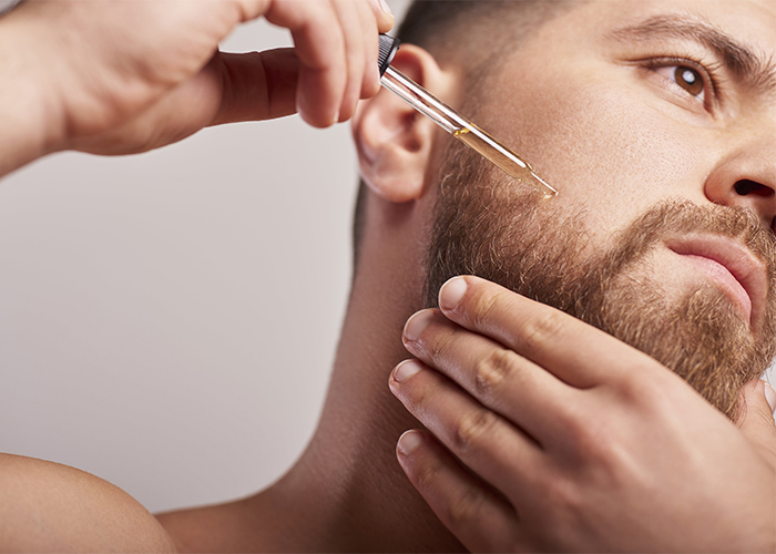 Man applying a homemade beard oil to his beard using a dropper.