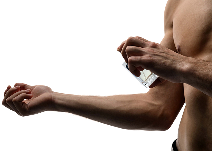 Man spraying DIY essential oil cologne blend on his arm