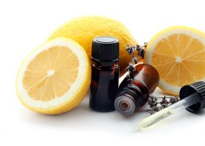 Bottles of lemon essential oil night serum next to freshly cut lemons