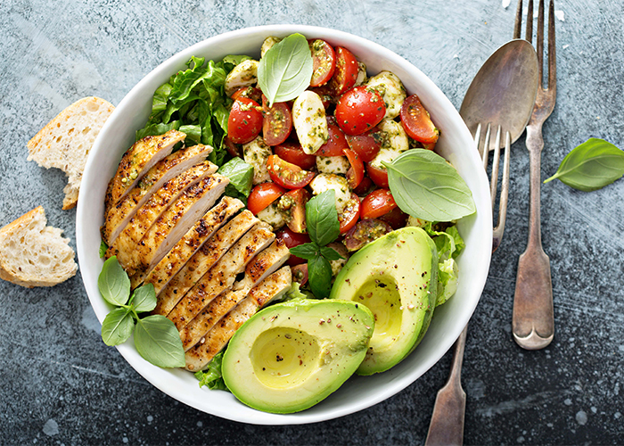 A homemade Paleo Taco Salad in a bowl with avocados, tomatoes, and chicken