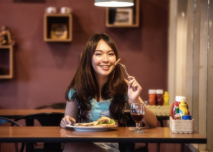 Woman happily eating a Paleo-friendly lunch