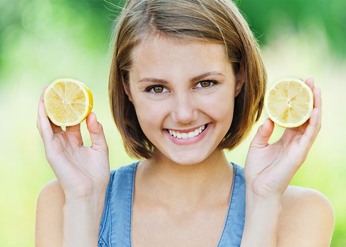Smiling woman holding up two halves of a lemon
