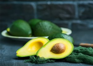 A halved avocado with a plate of fresh avocados in the background