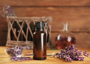 A bottle of lavender essential oil surrounded by dry lavender
