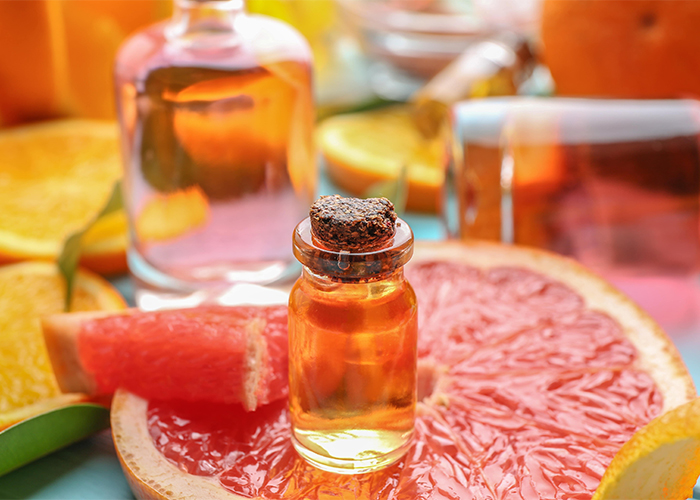 A bottle of grapefruit essential oil on top of a slice of grapefruit