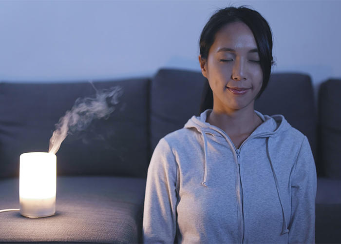 Woman meditating with a diffuser with her eyes closed