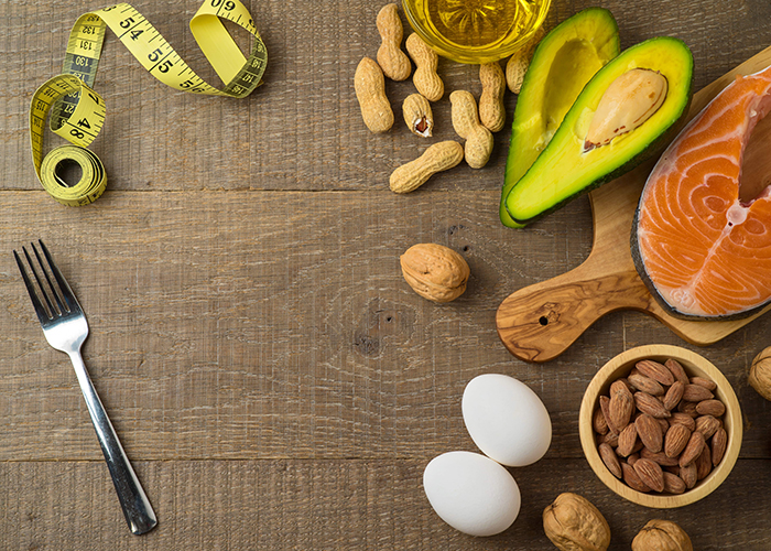 A flat-lay of Keto-approved foods including nuts, avocados, salmon, and eggs