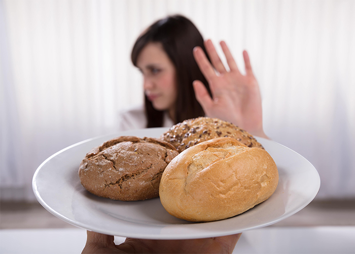 A woman on the AIP diet holding up her hand to reject a plate of three different types of bread