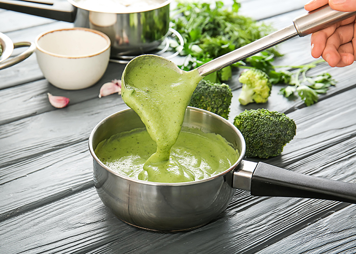 Woman mixing homemade keto broccoli and chedddar soup with a ladle