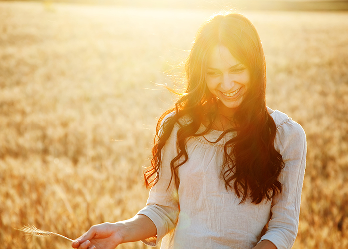 Woman smiling in a wheat field while holding a piece of wheat