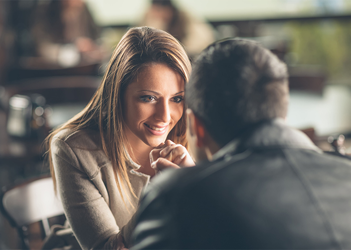Woman sitting across from her date smiling in a restaurant