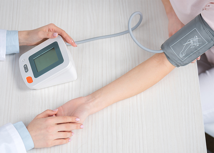 Doctor measuring a patient's blood pressure using a blood pressure machine.