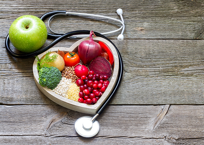 Paleo-approved fruits, vegetables, and grains in a heart shape next to a stethoscope