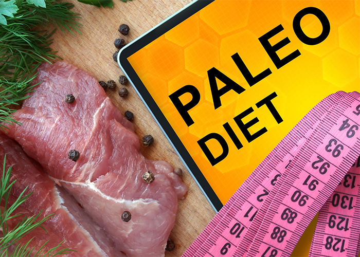 "A ""Paleo Diet"" sign with a measuring tape, fresh meat, and herbs"