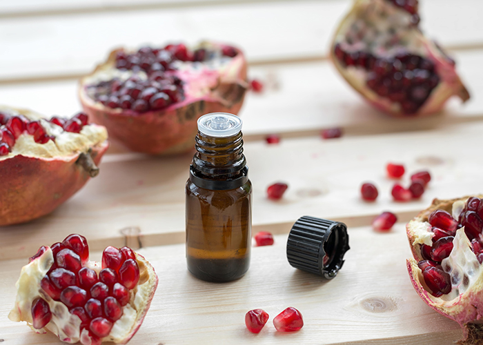 A bottle of pomegranate oil for stretch marks surrounded by freshly opened pomegranates