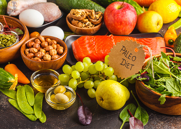 An array of healthy Paleo fresh foods including fruits, nuts, vegetables, and fish