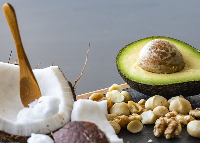 A halved coconut and avocado with mixed nuts scattered around