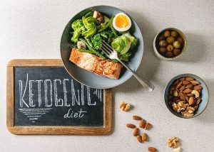 "A blackboard with ""ketogenic diet"" written on it next to a Keto-friendly salmon and salad lunch, and nuts for snacking"