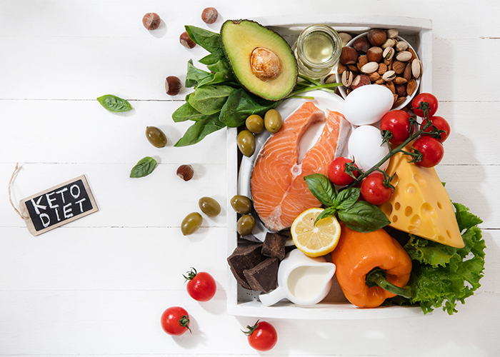 A box of ingredients used in Ketogenic recipes such as fresh vegetables, nuts, cheese, and olives