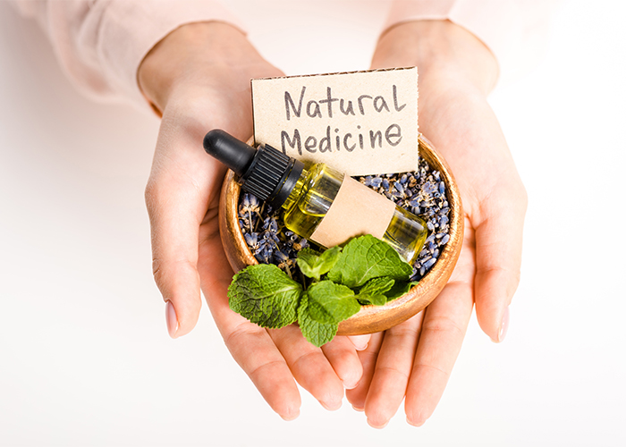 "Woman holding a wooden bowl with a dropper bottle of essential oil filled with dried lavender and the sign ""Natural Medicine"""