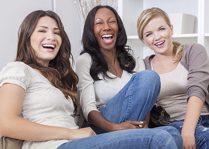 Three middle-aged female friends sitting on a couch laughing