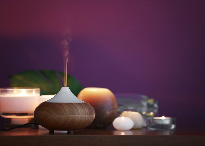 An aromatherapy oil diffuser surrounded by different types of candles on a bedside table