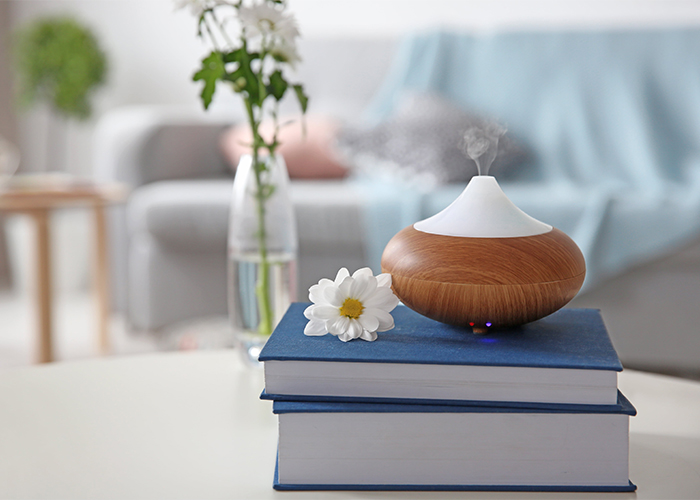 An aromatherapy diffuser with a bergamont essential oil blend for peaceful sleep on a stack of books in the lounge room