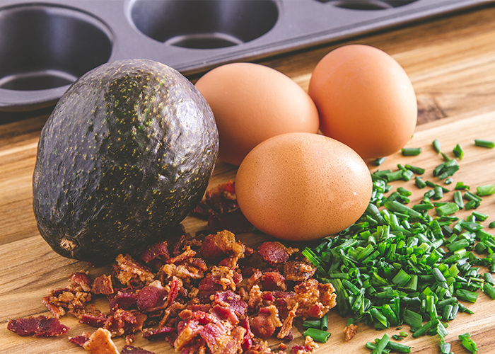 Ingredients for a Keto breakfast burrito prepped on a wooden board including fried bacon, spring onions, eggs, and an avocado