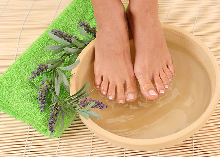 Feet with a French pedicure soaking in lavender essential oil infused water next to a towel and a sprig of lavender