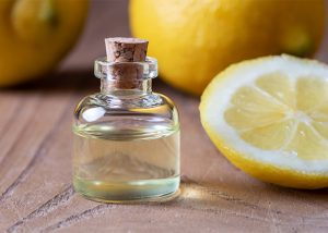 A small bottle of hand-poured lemon essential oil next to freshly cut lemons