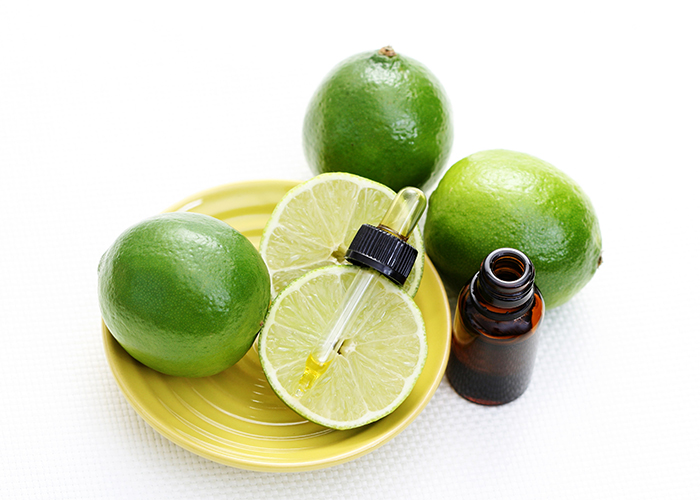 A bottle of lime essential oil with a dropper next to a plate of limes