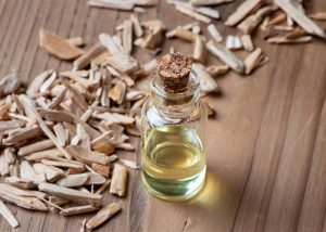 A bottle of sandalwood essential oil next to a pile of sandalwood pieces
