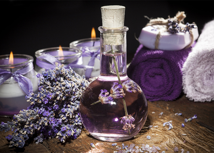 A glass potion bottle filled with homemade lavender essential oil next to a variety of lavender essential oil products such as candles and soaps.