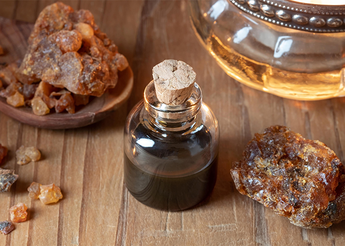 A bottle of hand-poured myrrh essential oil surrounded large and small pieces of myrrh