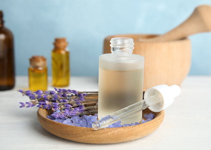 A cloudy bottle of lavender essential oil with a dropper on a wooden plate filled with lavender bath crystals and sprigs of lavender