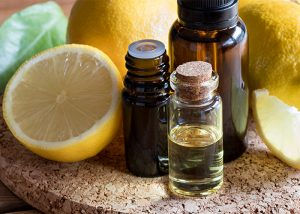 Different sized bottles of lemon essential oil on a cork plate