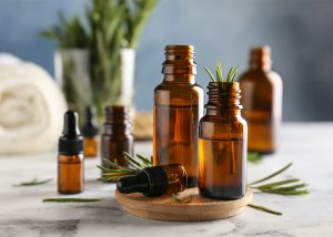 An assortment of amber bottles filled with rosemary essential oils with sprigs of rosemary