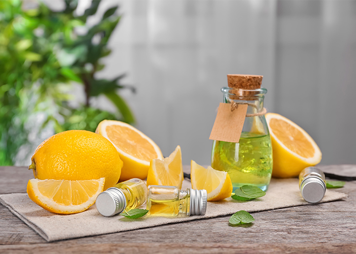 A table with bottles of lemon essential oil and cut up pieces of lemon