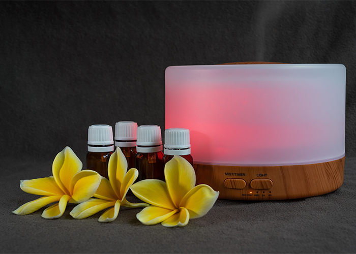 Amber colored bottles of a homemade bergamot essential oil diffuser recipe next to an electric diffuser and fresh flowers